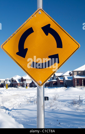 Roundabout reflective sign in Canadian suburb in winter - Stock Photo