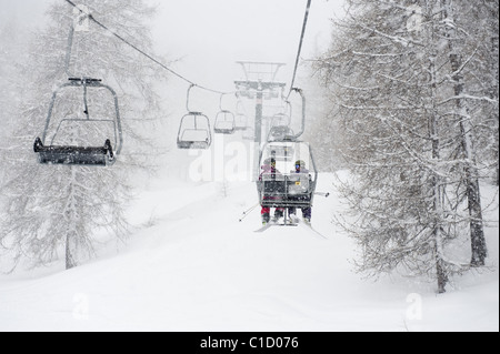 Two male free skiers sitting in the chairlift among snowy trees in Argentera, Italy - Stock Photo