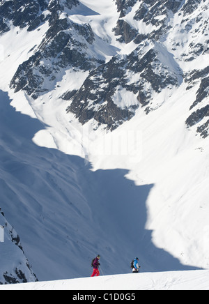 A free skier and a snowboarder hiking in the wintery mountain landscape of Serre Chevalier, France. - Stock Photo