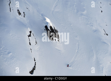 A free skier skiing down a steep mountain face at Serre Chevalier, France - Stock Photo