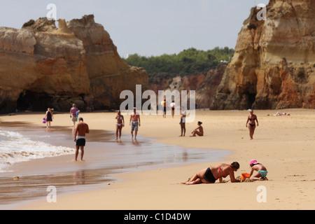 People walk along the beach. Mom and daughter build a figure from the sand close to Praia Da Rocha. Portimao, Algarve, - Stock Photo