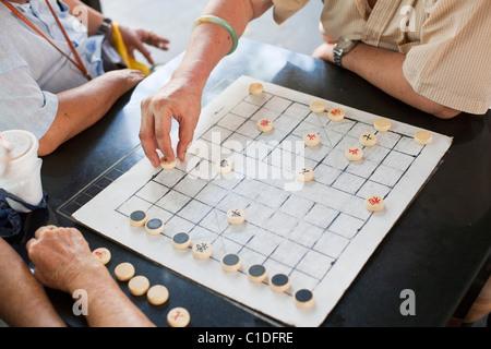 Men playing Xiangqi (Chinese chess) in Chinatown, Singapore - Stock Photo