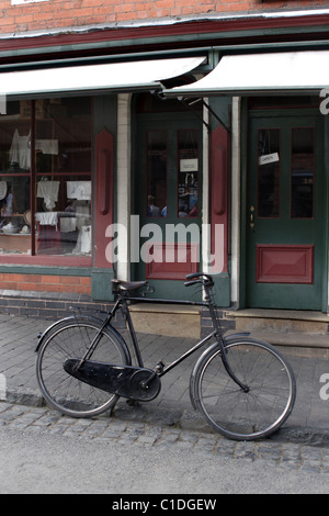 Old cycle outside shop - Stock Photo