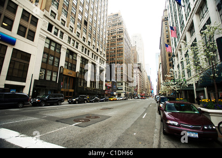 Cars parked on either side of a street in New York city Manhattan with tall buildings skyscrapers - Stock Photo