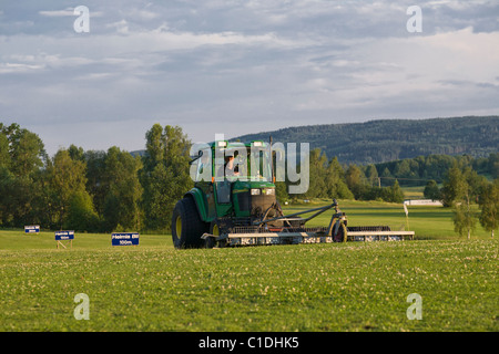 Tractor gathering golf balls at a driving range at the end of the day in Varmland, Sweden. - Stock Photo