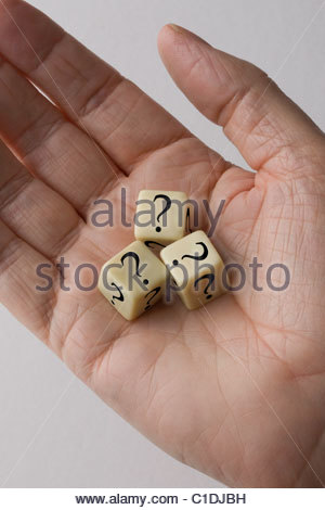 Three dice with questions marks on them in the palm of a mans hand. - Stock Photo