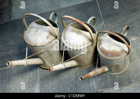 Three galvanised gardeners Watering Cans, a One Gallon, One and a Half Gallon and a Two Gallon on a slate floor. - Stock Photo