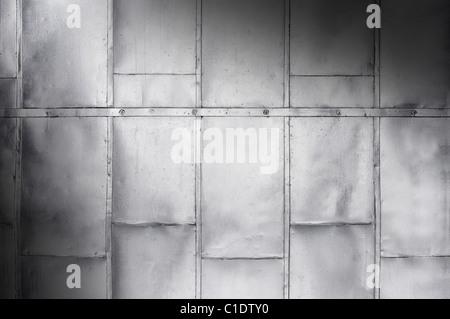 Metal panels on industrial door or wall lit diagonally - Stock Photo