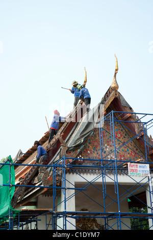 Workers Repairing Temple Roof at Wat Pho Bangkok - Stock Photo