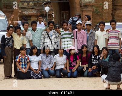Burmese tourist group begin photographed outside Htilominlo temple, southwest Bagan, Myanmar Burma - Stock Photo