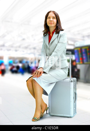 young businesswoman sits on silver suitcase in airport