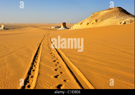 Tracks on a sand dune and an chalk rock formation in the White Desert national Park, western of Egypt - Stock Photo