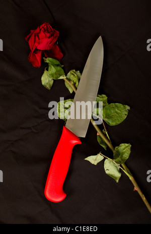 Big kitchen knife and almost withered red rose - Stock Photo
