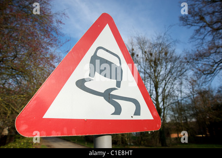 A road sign warning of a slippery road ahead, Warwickshire, England, UK - Stock Photo