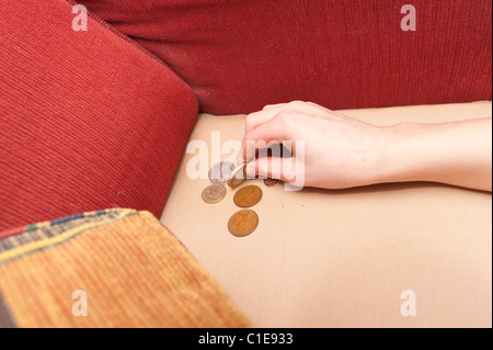 Lost money being found under a cushion on the sofa having dropped out of someones pocket - Stock Photo
