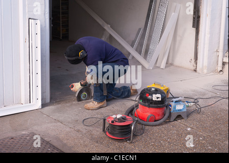 A builder using an angle grinder to cut through a concrete floor in the Uk - Stock Photo
