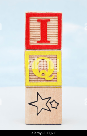Stack of 3 alphabet letter blocks with letters spelling IQ star against a blue sky background - Stock Photo