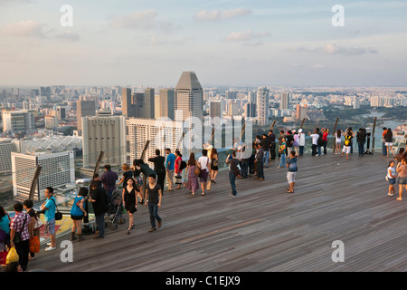 Visitors look out over Singapore skyline from observation deck of the Marina Bay Sands SkyPark.  Marina Bay, Singapore - Stock Photo