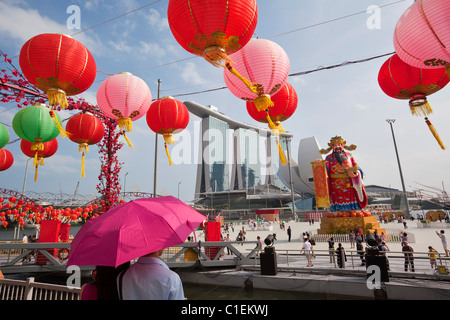 A couple look out at River Hongbao decorations (Chinese New Year) and the Marina Bay Sands Hotel.  Marina Bay, Singapore - Stock Photo