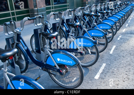 City of London , Moorgate Station , Boris or Barclays bikes for hire , transport bicycle or cycles , stands awaiting - Stock Photo