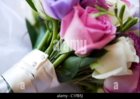 brides bouquet with pink white cream roses flowers and ivory ribbon wrapped around the stems - Stock Photo
