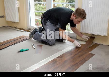 An interior designer laying the flooring - Stock Photo