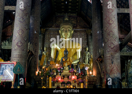 A beautiful large gold Buddhist statue decorates a room inside historic & ancient Wat Xieng Thong temple in Luang - Stock Photo
