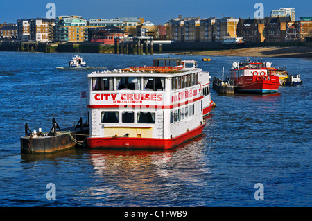 City cruise riverboat M.V. Eltham moored on River Thames with modern apartments along the banks, London, UK - Stock Photo