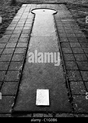 High contrast black and white image of the most simple minigolf pitch reaching goal aim target - Stock Photo