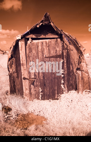 Fishermans hut from upturned boat at Lindisfarne Holy Island shot in infrared - Stock Photo