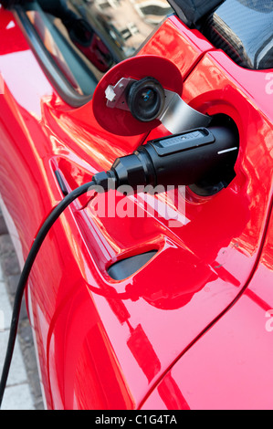 Electric Tesla sports car being recharged at public recharging point in Amsterdam The Netherlands - Stock Photo