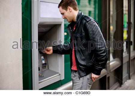 A young man using a cash machine - Stock Photo