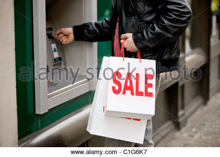 A young man using a cash machine, holding carrier bags - Stock Photo