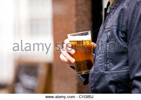 A young man drinking a pint of beer - Stock Photo