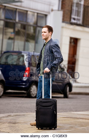 A young man standing in the street, holding his suitcase - Stock Photo