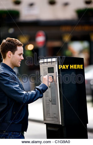 A young man putting coins in a parking meter - Stock Photo