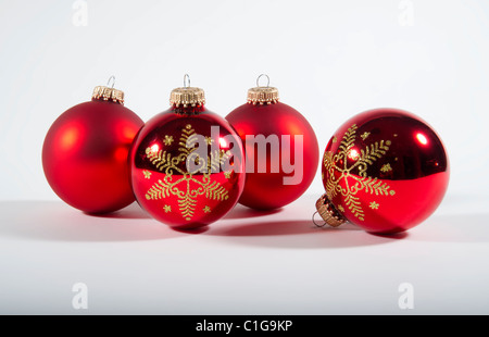 4 red Christmas tree baubles - Christmas decorations pair of satin and 2 shiny with gold snowflake paterns - Stock Photo