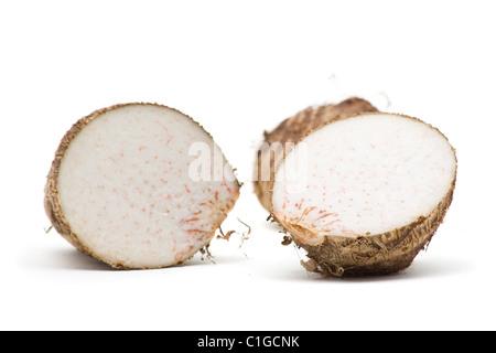 Fresh taro root cut in half over white background - Stock Photo