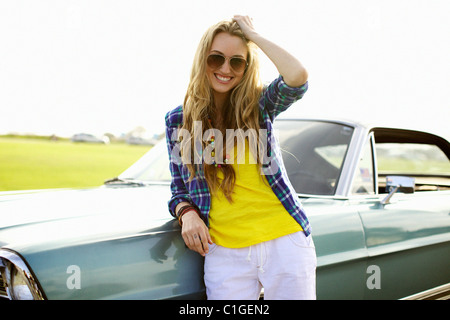 Smiling Caucasian woman leaning against car