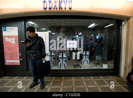 A man reads a book outside a department store that has switched off its lights to safe electricity in Tokyo - Stock Photo