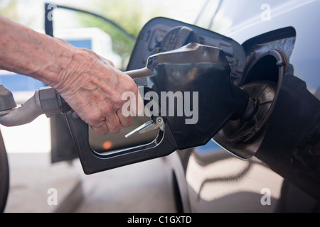 Woman filling car at a gas station - Stock Photo