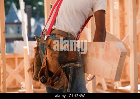 Mid section view of a carpenter carrying a wooden rafter - Stock Photo
