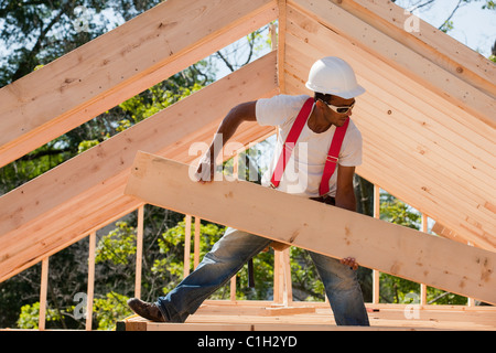 Carpenter carrying a wooden rafter - Stock Photo