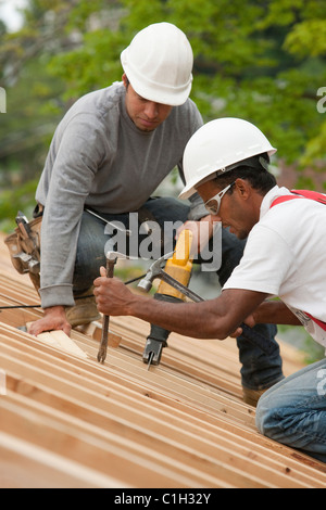 Carpenters using a sawzall and a pry bar on the roof of a house under construction - Stock Photo