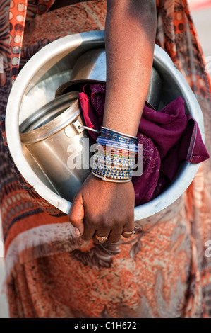 Indian woman holding a metal cooking pot with bangles on her arm. materila - Stock Photo