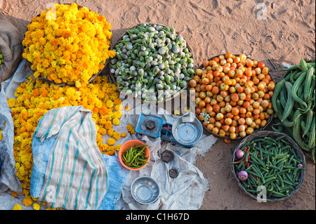 Indian woman selling vegetables and flowers at a street vegetable market in Puttaparthi, Andhra Pradesh, India - Stock Photo