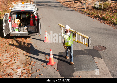 Cable installer carrying a ladder - Stock Photo