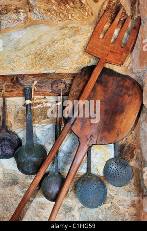 Picture of traditional oven and cooking utensils arranged against a stone wall - Stock Photo