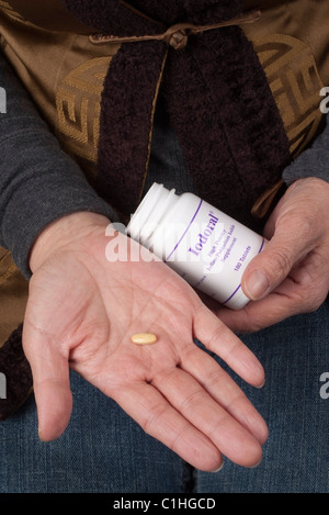 Woman holding Potassium Iodide tablets purchased after the Japanese Nuclear accident in March 2011 - Stock Photo