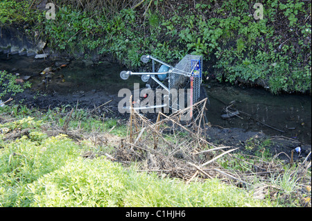 Shopping trolley dumped in stream, Anti Social behavior , fly-tipping - Stock Photo